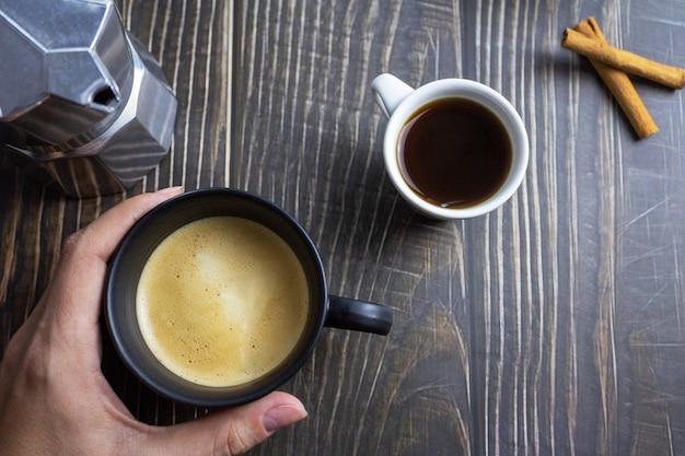 Mano che tiene una tazza di caffè sul tavolo di legno vista dall'alto