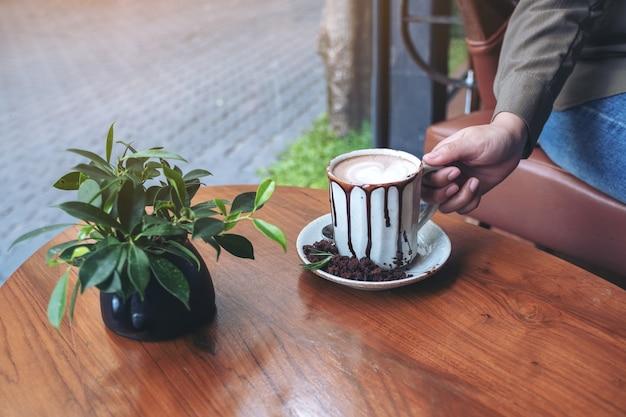 Mano che tiene una tazza di cioccolata calda sul tavolo di legno nella caffetteria
