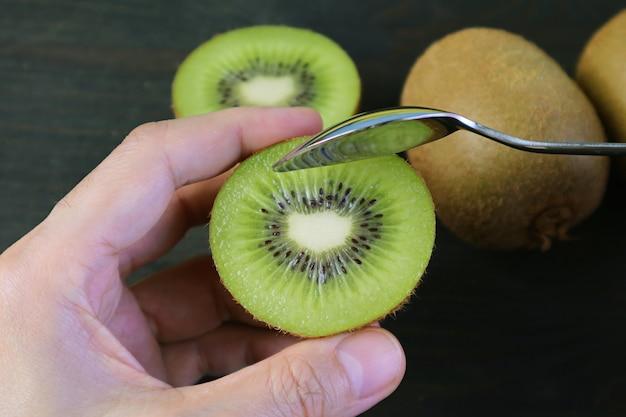 Mano che tiene il kiwi tagliato scavando con un cucchiaio su sfondo nero