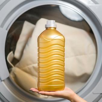 Vista frontale della bottiglia detergente della tenuta della mano Foto Premium