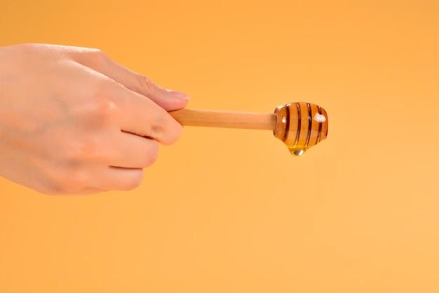 Mano che tiene il mestolo con miele