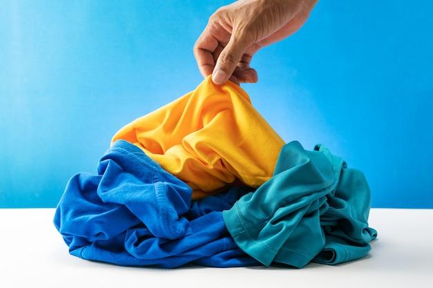 Passi la tenuta della lavanderia sporca sulla tavola bianca fondo del blu.