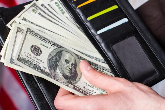 Mano che tiene dollari e portafoglio. portafoglio con carte e denaro. è stato un mese intenso. abbastanza soldi per una vacanza adeguata.