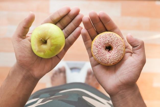 Mano che tiene ciambelle e mela a portata di mano sulla scala del peso.