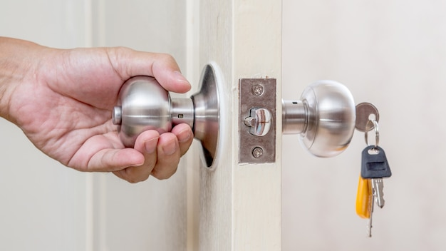 Mano che tiene la maniglia della porta con chiavi