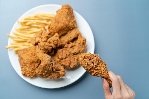 Mano che tiene le bacchette, pollo fritto croccante con patatine fritte nel piatto bianco su sfondo blu.