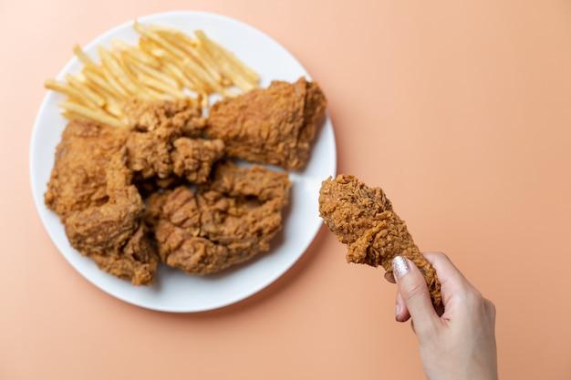 Mano che tiene le bacchette, pollo fritto croccante con patatine fritte nel piatto bianco su sfondo arancione.