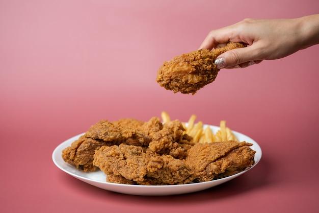 Mano che tiene le bacchette, pollo fritto croccante con patatine fritte nel piatto bianco su sfondo rosso.