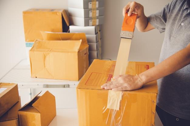 Mano che tiene il nastro adesivo per imballare i prodotti per preparare le spedizioni.