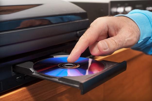 Mano che tiene l'inserimento di dvd sul lettore video