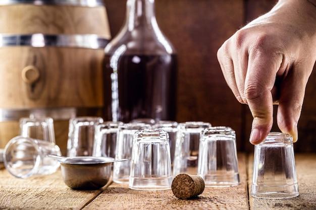 Mano che tiene il bicchiere vuoto a goccia, bevanda distillata di canna da zucchero, bottiglia sullo sfondo sfocato