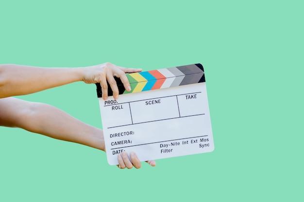 Mano che tiene il pannello dei colori dell'ardesia del film per l'industria cinematografica e televisiva