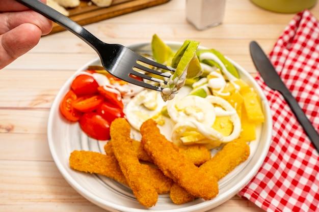Una mano che tiene una forchetta con un boccone di avocado e aioli e sullo sfondo un piatto con deliziosi bastoncini di pollo e insalata fresca di avocado, ciliegia, uova e formaggio. cibo sano di concetto.