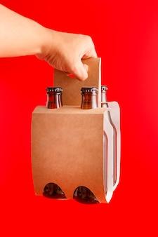 Mano che tiene una presentazione di quattro pack birra con sfondo rosso