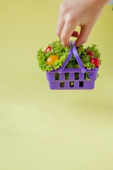 Mano che tiene la merce nel carrello di verdure fresche su sfondo giallo