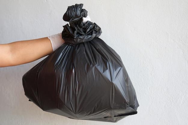 Isolato della borsa del nero dell'immondizia della tenuta della mano su fondo bianco