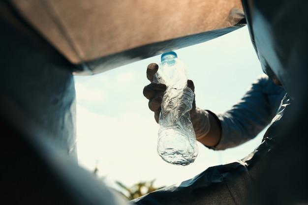 Putt della bottiglia della spazzatura della tenuta della mano dentro alla borsa nera
