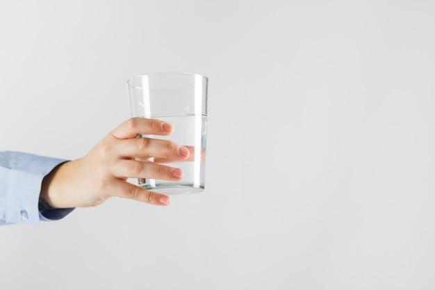 Mano che tiene il bicchiere d'acqua