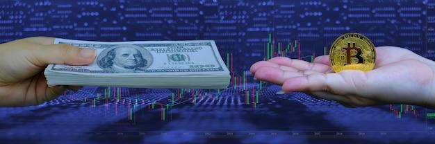 Mano che tiene la criptovaluta bitcoin dorata e la valuta cartacea sullo sfondo del grafico di trading