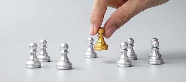 Mano che tiene pezzi di pedina degli scacchi dorati o uomo d'affari leader con uomini d'argento. vittoria, leadership, successo aziendale, squadra, reclutamento e concetto di lavoro di squadra