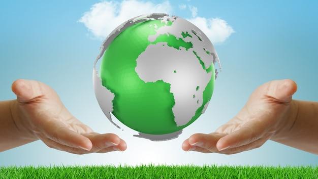 Mano che tiene la terra verde