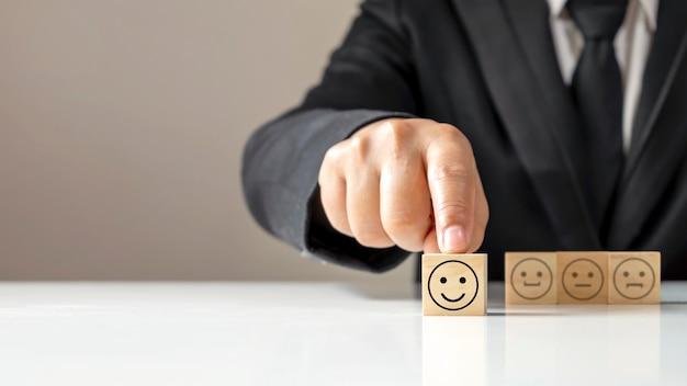 Mano che tiene l'icona felice su un cubo di legno sul tavolo, concetto di indagine sulla soddisfazione annuale aziendale.