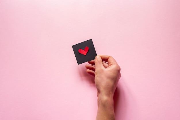 La mano che regge un cuore sul muro rosa, san valentino. flat lay