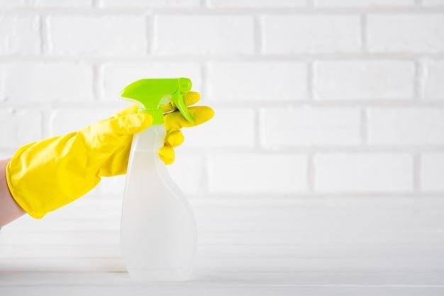 Mano che tiene uno spray per la pulizia della casa su uno sfondo chiaro.