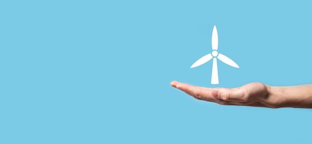 Mano che tiene un'icona di un mulino a vento che produce energia ambientale su sfondo blu.