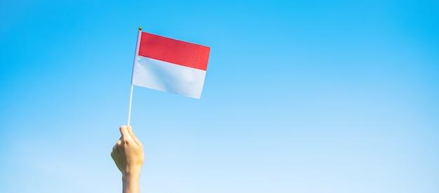 Mano che tiene la bandiera dell'indonesia sul fondo del cielo blu. festa dell'indipendenza dell'indonesia, festa nazionale e concetti di celebrazione felice