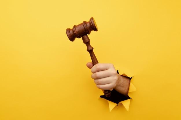 Mano che tiene un martello dei giudici attraverso la legge sul muro di carta gialla strappata e il concetto di giustizia