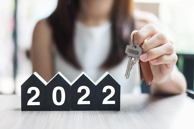 Chiave che tiene in mano e felice anno nuovo 2022 con modello di casa
