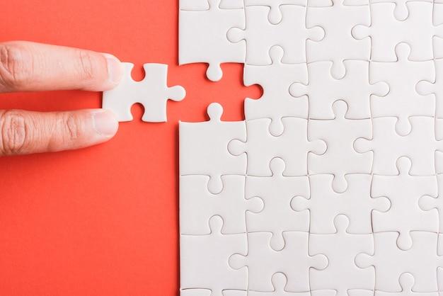 Ultimo pezzo con la mano che tiene in mano il gioco di puzzle con carta bianca, ultimi pezzi messi a posto per risolvere il problema, completare la missione