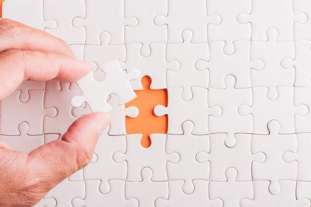 Ultimo pezzo che tiene in mano il gioco di puzzle di carta bianca, ultimi pezzi messi a posto per risolvere il problema, completare la missione