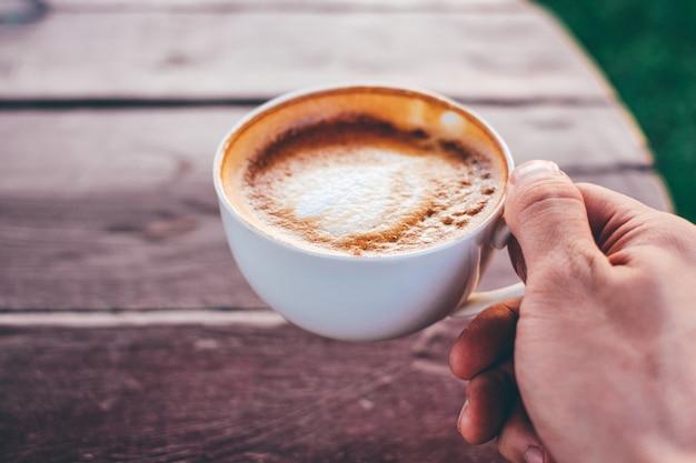 Passi la tenuta della tazza di caffè del latte sulla tavola di legno a tempo la mattina