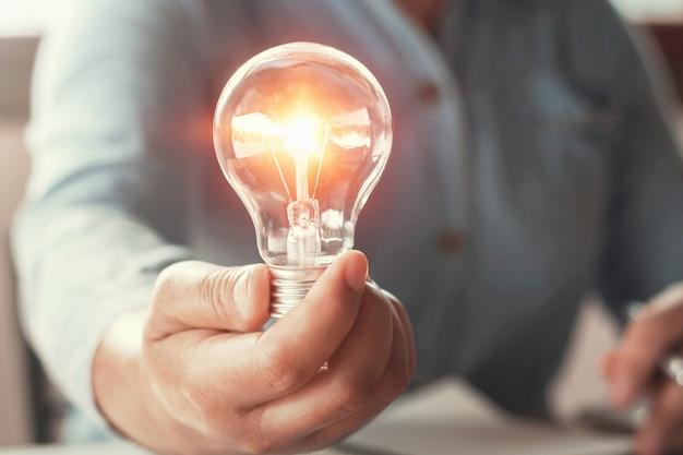 Mano che tiene il concetto di energia energia della lampadina