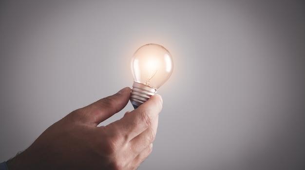 Mano che tiene la lampadina. ispirazione, creatività
