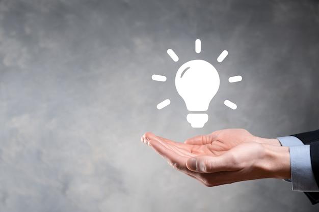 Mano che tiene la lampadina. simbolo di idea intelligente isolato. innovazione, icona della soluzione. soluzioni energetiche. concetto di idee di potere. lampada elettrica, invenzione tecnologica. palmo umano. ispirazione aziendale.