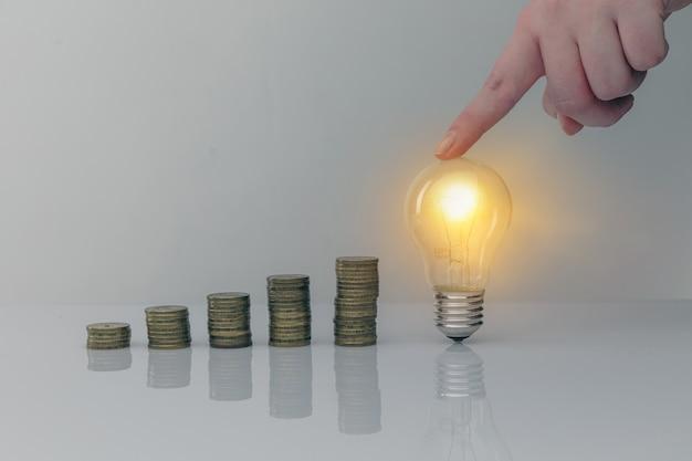 Mano che tiene una lampadina con pila di monete. idee creative per risparmiare denaro concetto. gestione del denaro per il futuro.