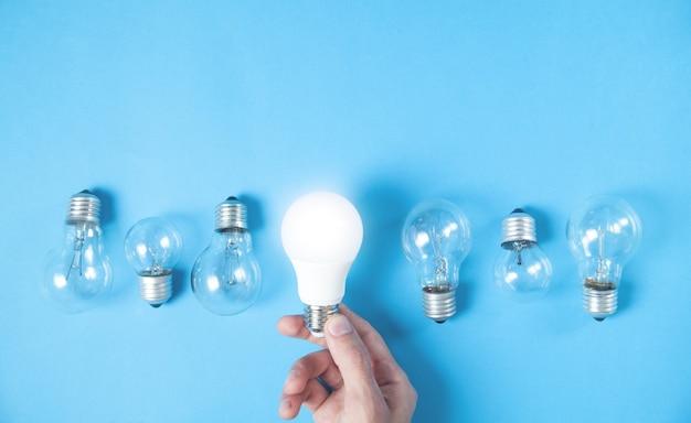 Mano che tiene la lampadina con luce su altre lampadine