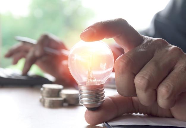 Mano che tiene le lampadine incandescente e utilizzando la calcolatrice. idea, creatività e risparmio energetico