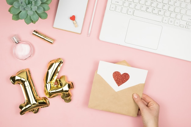 Passi la tenuta della busta di amore sulla tavola pastello rosa con altri rifornimenti Foto Premium