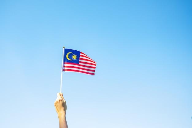 Mano che tiene la bandiera della malesia sul fondo del cielo blu. giornata nazionale della malesia di settembre e giorno dell'indipendenza di agosto
