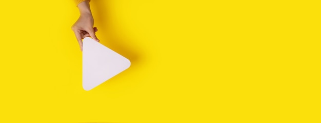 Mano che tiene l'icona del pulsante del lettore multimediale su sfondo giallo alla moda, mockup panoramico