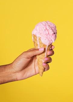 Mano che tiene un gelato che si scioglie