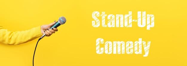 Mano che tiene il microfono su sfondo giallo, immagine panoramica con scritta commedia in piedi