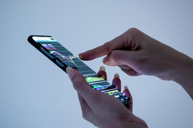 Mano che tiene il telefono cellulare tecnologia aziendale, grafico, finanziario e del mercato azionario