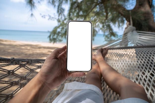 Mano che tiene il cellulare simulato con schermo bianco mentre si posa sull'oscillazione dell'amaca tra gli alberi sulla spiaggia.