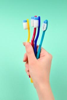Mano che tiene più spazzolini da denti isolati
