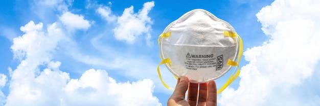 Mano che tiene la maschera n95 per la protezione da inquinamento, virus, influenza e coronavirus (covid-19). protezione pm 2.5. maschera viso aria. maschera medica.